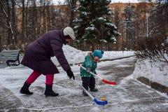 祖母和小两岁的孙子获得打曲棍球的乐趣在公园在冬天 免版税库存图片
