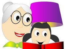 祖母或老师读一本小女孩书 免版税库存照片