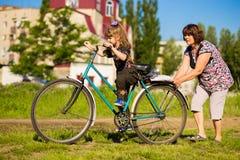 祖母教小孙女骑自行车 图库摄影