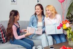 祖母母亲和给当前箱子的在家一起女儿庆祝坐的女孩愉快的老婆婆和的妈妈 库存图片