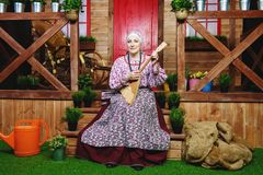 祖母演奏俄式三弦琴 图库摄影