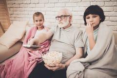 祖父、孙子和孙女在家 祖父和孩子观看在电视的电影并且吃玉米花 库存照片