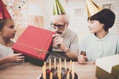祖父、孙子和孙女在家 非洲裔美国人气球美丽的生日蛋糕庆祝巧克力杯子楼层女孩藏品家当事人当前坐的微笑的包围的时间对年轻人 免版税库存照片