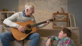 祖父为他的吉他的,音乐孙子使用 一个年轻肥胖人坐与他的祖父的避风港 教 影视素材