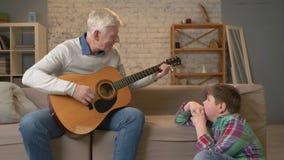 祖父为他的吉他的,音乐孙子使用 一个年轻肥胖人坐与他的祖父的避风港 教 股票录像
