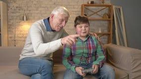 祖父享受他的控制台比赛的孙子胜利  老人坐有一个年轻肥胖男孩的长沙发 股票录像