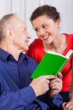 祖父和孙女阅读书 库存照片