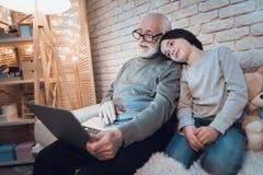 祖父和孙子在与家庭的skype在家谈话在晚上 库存照片