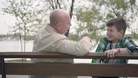 祖父和孙子在公园在河附近坐长凳,老人讲有趣故事对男孩 股票录像