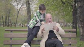 祖父和孙子在公园坐长凳,读男孩的老人书 儿童身分与 股票视频