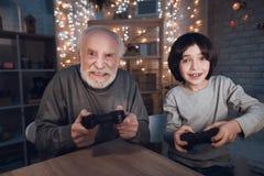 祖父和孙子在晚上在家打电子游戏 免版税图库摄影