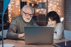 祖父和孙子在晚上在家观看在膝上型计算机的录影 图库摄影