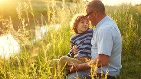 祖父和孙子坐河岸 成熟人和卷发的男孩放松的坐草 股票录像