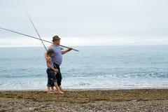 祖父和孙子捕鱼 库存图片