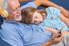 祖父和孙子有耳机的听音乐拥抱 免版税库存图片