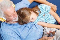 祖父和孙子有耳机的听音乐拥抱 免版税图库摄影
