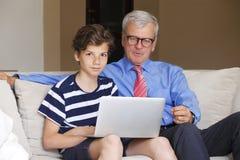 祖父和孙子有膝上型计算机的 免版税库存照片
