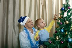 祖父和孙子装饰圣诞节云杉 库存图片