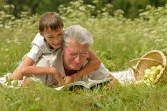 祖父和孙子阅读书 免版税库存照片