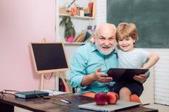 祖父和小孩在类学会 谢谢老师 愉快的逗人喜爱的聪明的男孩和老家庭教师有书的 ? 免版税图库摄影