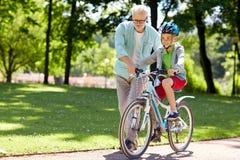 祖父和男孩有自行车的在夏天停放 库存图片