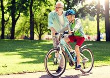 祖父和男孩有自行车的在夏天公园 免版税库存图片