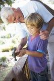 祖父和Grandsonon大厦一起树上小屋 免版税库存图片