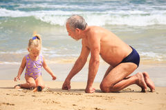 祖父小女孩坐湿沙子神色在壳由海浪 免版税库存照片
