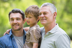 祖父微笑在公园的父亲和儿子 库存图片