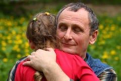 祖父拥抱的孙女 免版税图库摄影