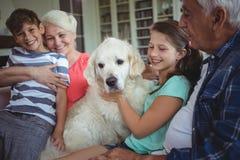 祖父母和孙坐有爱犬的沙发 免版税库存图片