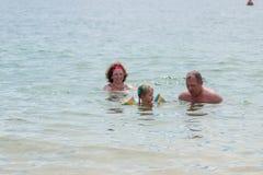 祖父母和孙女游泳在海,他们微笑和happyness 库存照片