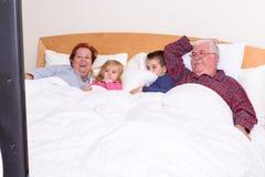 祖父母在床上的看电视与他们的盛大孩子 免版税库存照片
