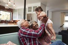 祖父母坐在家使用与小孙女的沙发 免版税库存照片