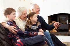 祖父母坐看与孙的沙发电视 免版税库存照片