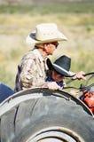 祖父的男孩一点乘驾拖拉机 免版税库存图片