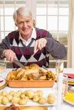 祖父雕刻的烘烤火鸡的画象在圣诞节的 免版税库存图片