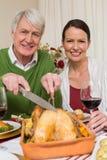 祖父雕刻的鸡,当喝红葡萄酒时的妇女 库存照片