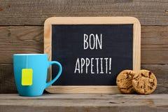 祝愿在小黑板、茶和曲奇饼的好的妙语appetit 免版税库存照片