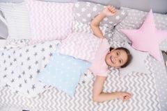 祝愿她的早晨好 在床放置的女孩孩子她的卧室 孩子醒和有很多能量 宜人的时间放松舒适卧室 库存图片