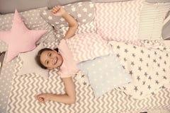 祝愿她的早晨好 女孩孩子在床放置她的卧室 孩子醒和有很多能量 宜人的时间放松舒适卧室 库存照片