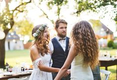 祝贺新娘和新郎的女孩在结婚宴会在后院 免版税库存图片