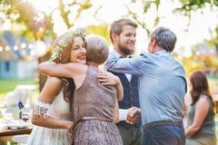 祝贺新娘和新郎的客人在结婚宴会外面在后院 图库摄影