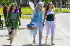 神仙服装的三个女孩,小孩子的党的设计卡通者沿路走在城市, 库存图片