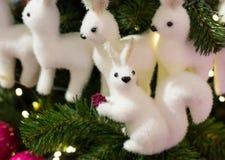 神仙的在拿着背景的一个云杉的分支的圣诞树玩具白色灰鼠小开会一个土包子 免版税图库摄影