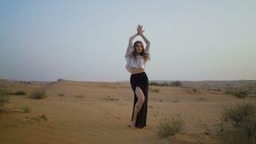 神奇俏丽的女孩在沙漠走 美丽的妇女跳舞在日落 慢的行动 股票录像