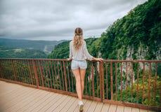 神奇夫人去跨接,有金发和长的腿的夫人,旅游在便服,明亮的颜色和 免版税库存照片