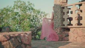 神奇女孩在一个石色的专栏后站立,穿戴在有金领带的一件豪华桃红色礼服,举行长 股票视频