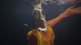 神奇妇女游泳喜欢美人鱼在水下在黑暗的背景 股票录像