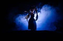 神奇妇女,可怕鬼魂玩偶妇女恐怖场面深蓝背景的与烟 库存照片